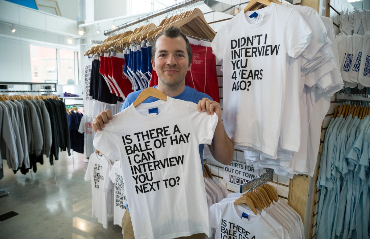 Mike Draper, owner of RAYGUN, shows off his latest line of T-shirts for out-of-state media in downtown Des Moines's East Village district.