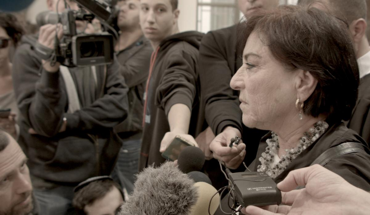 Israeli lawyer Lea Tsemel is shown in Advocate speaking to a scrum of reporters at a Jerusalem courthouse.