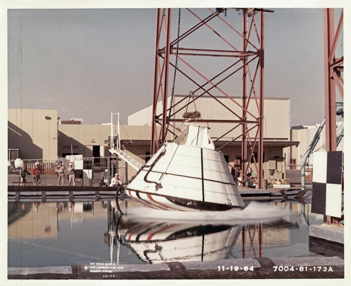 Drop testing of an Apollo command module prototype at the North American Aviation facility in Downey, Calif., November 1964. A large water tank and 150-foot drop tower were used to test the capsules.
