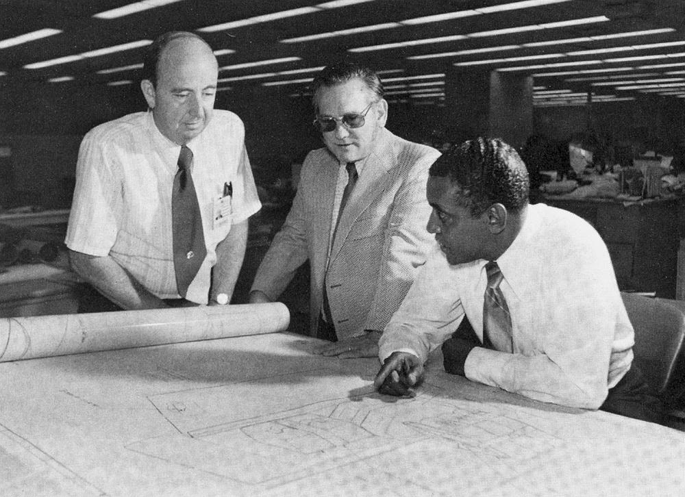 Chuck Lowry (left) reviews designs on a drafting board with Carlos Moore and Kel Shaw (right).