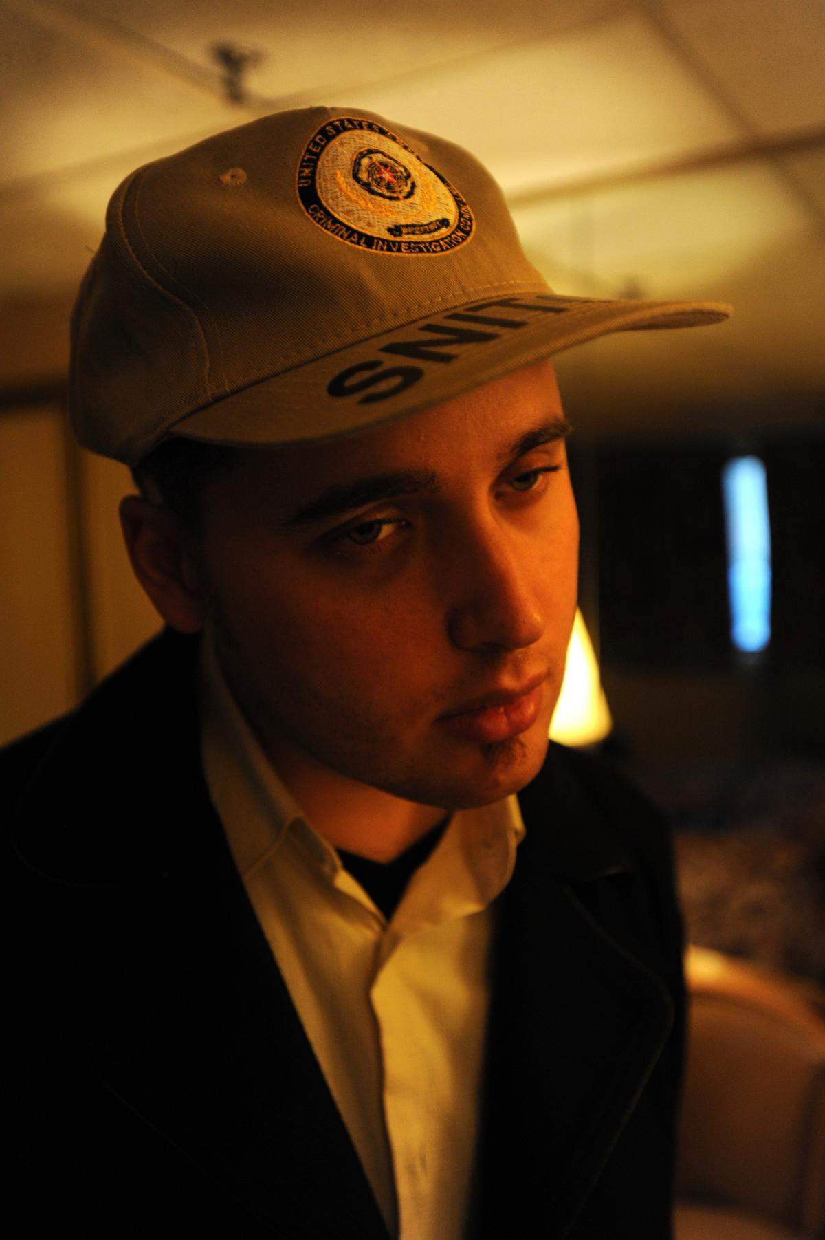 Adrian Lamo in a motel room on Long Island, N.Y. Lamo tried to make light of his reputation as a snitch, even wearing a hat that labeled him as such.