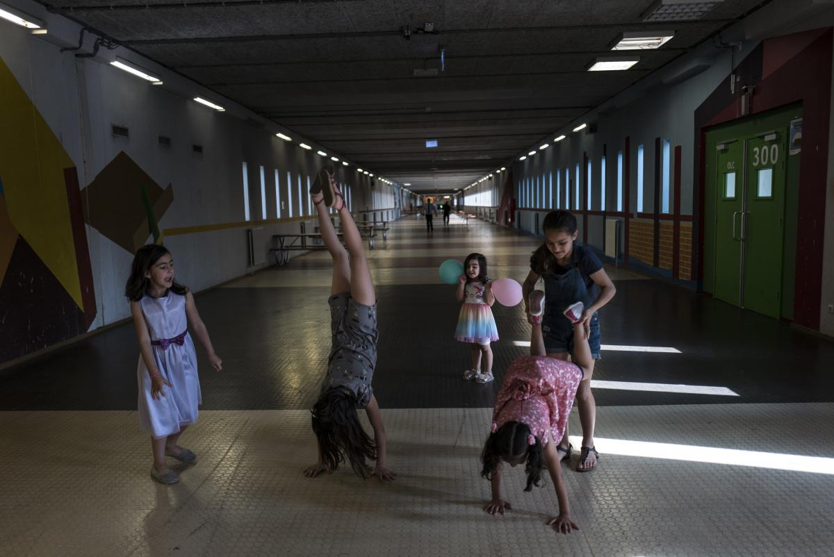 Syrian refugee girls (from left) Shahd Alamar, 8, Lana Alkhawaja, 9, Maya Alamar, 4, Amal Sakkal, 8, and Hala Alhalaby, 8, play in a hallway at the former prison of Bijlmerbajes in Amsterdam.