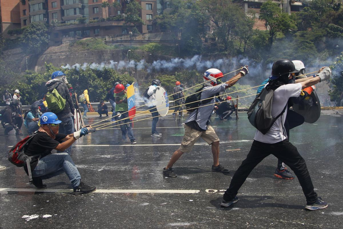 Anti-government protesters aim a giant slingshot with a glass bottle containing fecal matter at security forces in Caracas, Venezuela, on May 10.