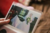 Pauline shows a photograph from her wedding day. After the wedding, her husband, David, moved into a room with Pauline in her caretaker's home. Now they talk on the phone most nights and David sends her cards to stay in touch.
