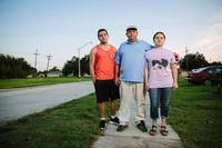Igor Depaula, 17, father Jose Depaula, 50, and mother Francisca Depaula, 35, pose on the sidewalk near their home on Schnell Drive.