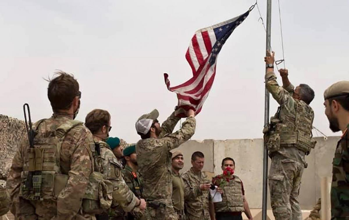 The U.S. flag is lowered as American and Afghan troops attend a handover ceremony at Camp Anthonic in the southern province of Helmand on May 2. After 20 years of war in Afghanistan, U.S. forces now number just a few thousand, down from a peak of more tha