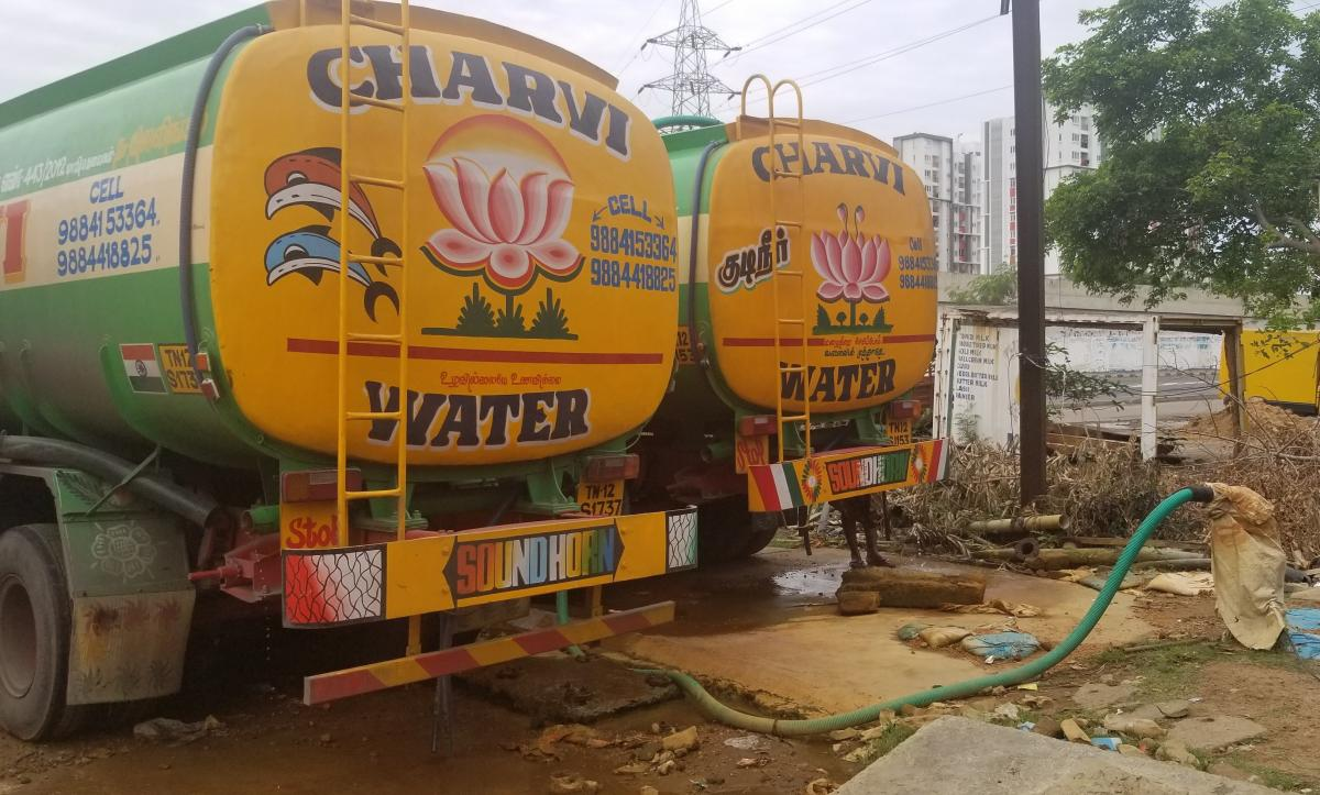 Private water tanker trucks fill up at a bore well on Chennai's outskirts. The area was once a lush farming village but has become part of Chennai's expanding urban periphery. Locals are drilling bore wells to sell their groundwater. It's more profitable