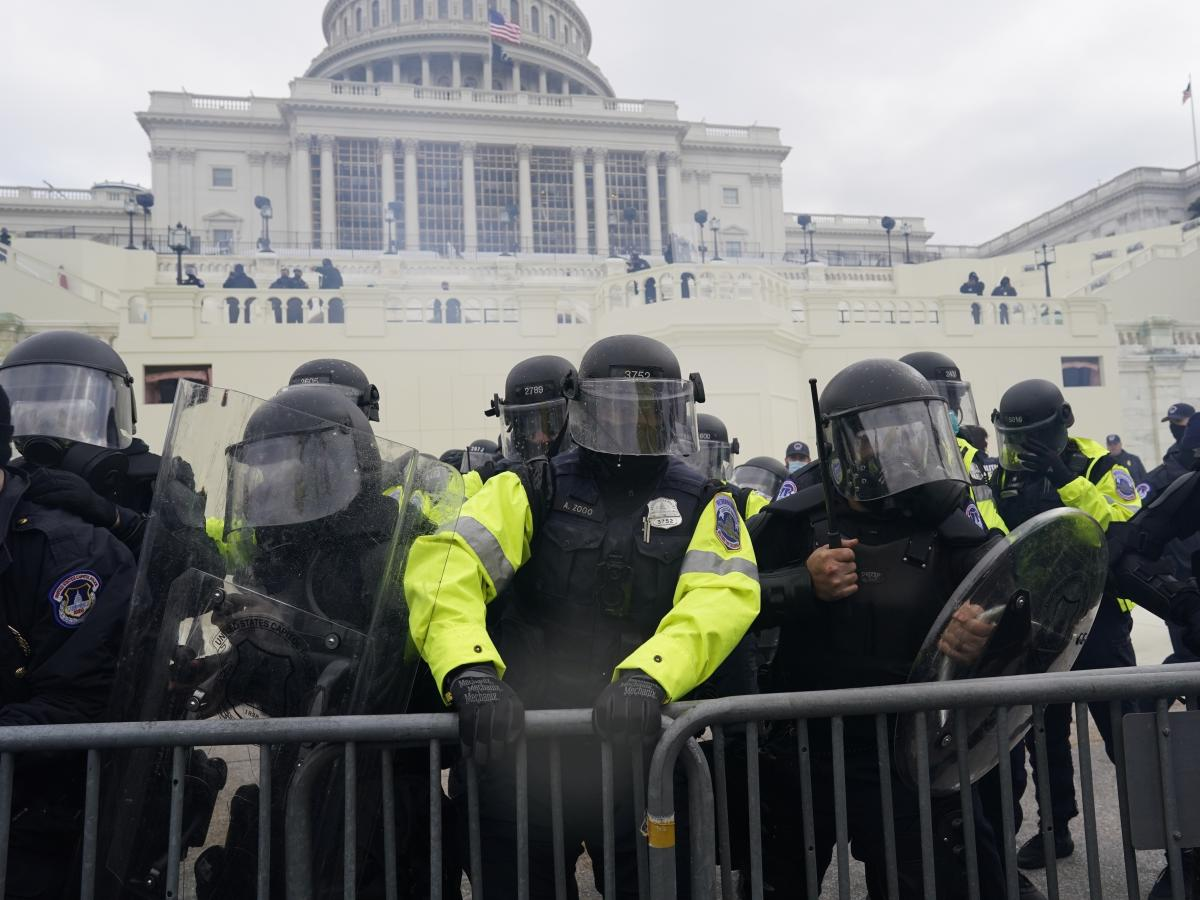 Law enforcement, including Capitol Police officers, try to hold back rioters at the Capitol on Jan. 6.