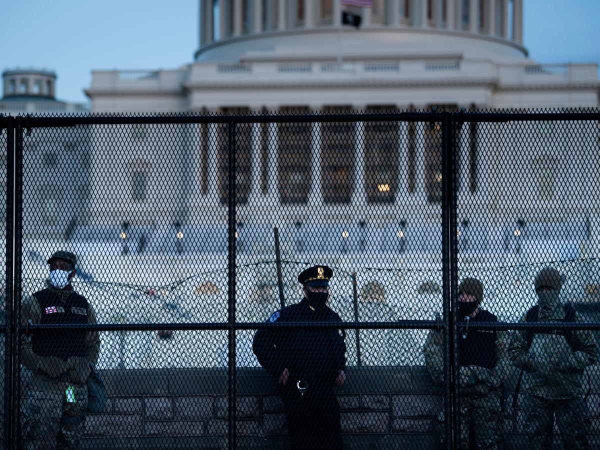 A Capitol Police officer stands with members of the National Guard behind a fence surrounding the Capitol on Jan. 7, a day after the insurrection.