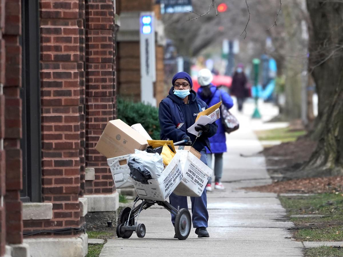 """A U.S. postal worker delivers packages, boxes and letters in Chicago's Hyde Park neighborhood shortly before Christmas. The U.S. Postal Service said it faces """"unprecedented volume increases and limited employee availability due to the impacts of COVID-19."""