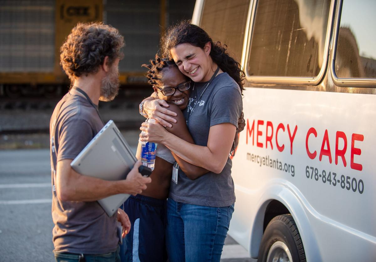 """Clinic patient Lawson (center) and nurse practitioner Fernandez de Narayan (right) share a hug outside the Mercy Care van, after the September check-in. """"We're trying to avoid emergencies, but we're also trying to build relationships,"""" says social worker"""