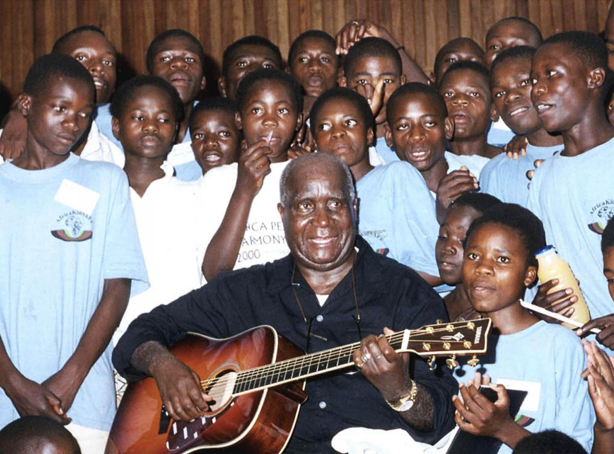 Former Zambian President Kenneth Kaunda plays the guitar at a workshop in Lusaka on November 10, 2000. He used his music to send messages, including how to combat AIDS.