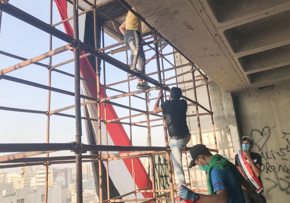 "Protestors climb scaffolding to reach the top of a Baghdad landmark known as the ""Turkish restaurant building."" It has no electricity, elevators or even walls. The building looks over Tahrir Square and has been occupied by protesters to prevent security f"