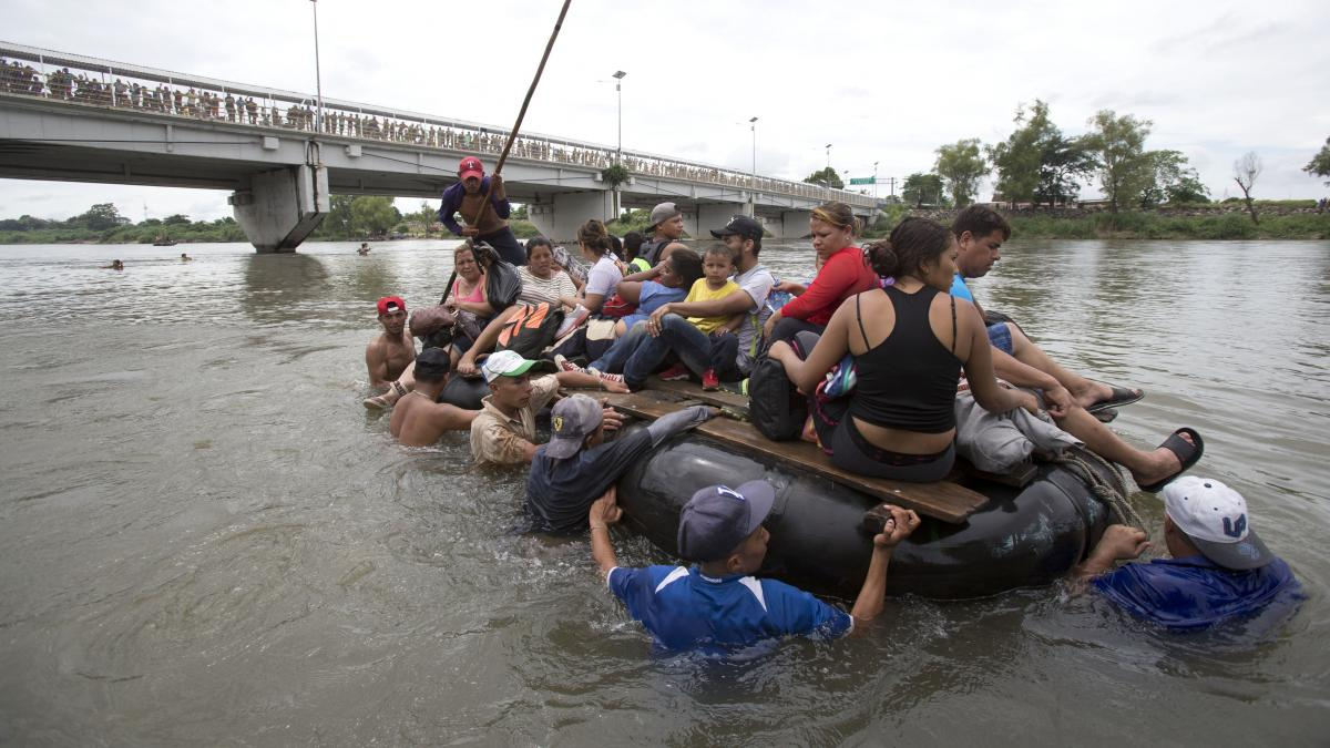 A group of Central American migrants cross the Suchiate River aboard a raft, on the the border between Guatemala and Mexico, in Ciudad Hidalgo, Mexico on Saturday. After Mexican authorities slowed access through the border bridge to a crawl, hundreds of m