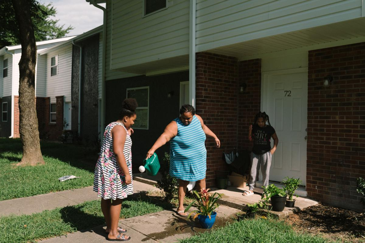 Talayla Feggins (left) and Tranese Feggins (right) help their mother, Harriet Feggins, water flowers at their home in west Atlanta. Harriet has shut off the power in some rooms and has hung blackout curtains to try to keep the house cool and her electric