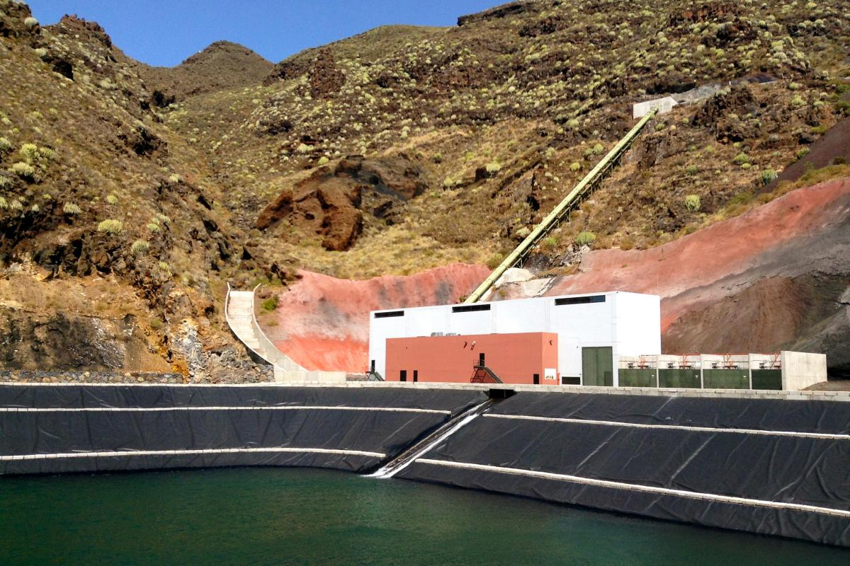 On days with little wind, water stored in El Hierro's upper reservoir is released through a pipe that cuts through the rocky hillside, falling through turbines and into this lower lake, for storage. On days with surplus wind energy, this water is pumped u