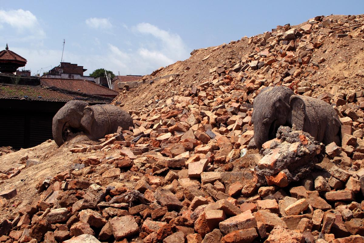 Two stone carved elephants look forlorn standing half-buried in the dusty debris of the monument they once guarded.