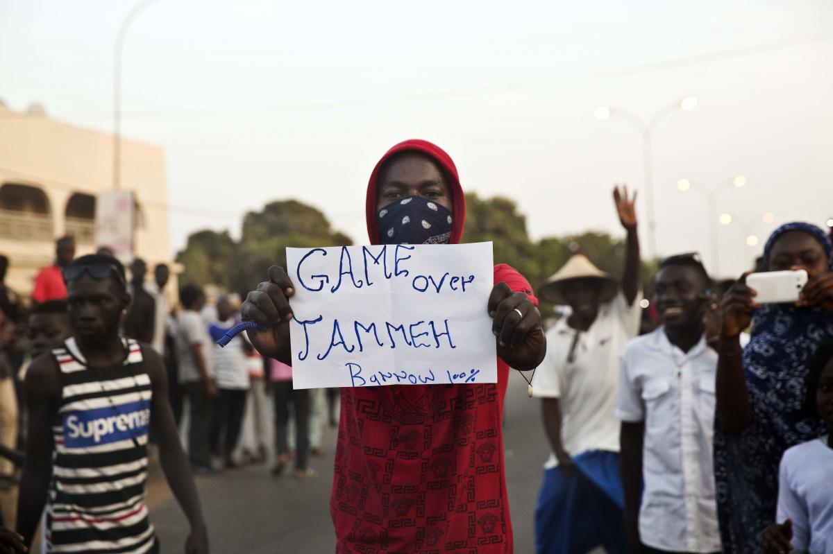 A man holds a banner Thursday as Gambians cheers in Serrekunda, Gambia.