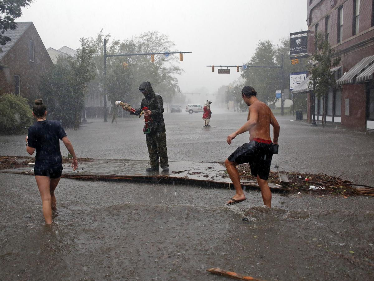 People survey damage and flooding brought by Hurricane Florence to Front Street in downtown New Bern, N.C.