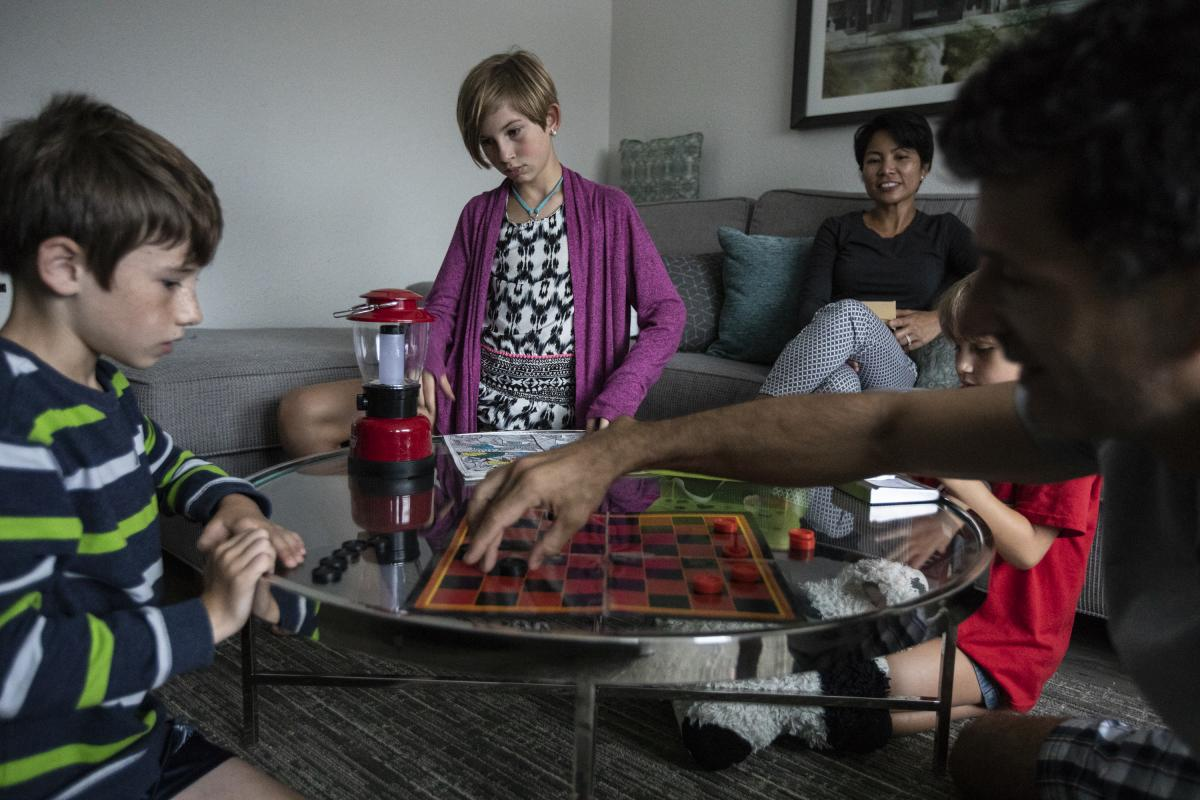 Marc Hohl (left) plays checkers with his father Greg as his sisters Abbie (center) and Ava watch with their grandmother Lola Grio in their hotel room.