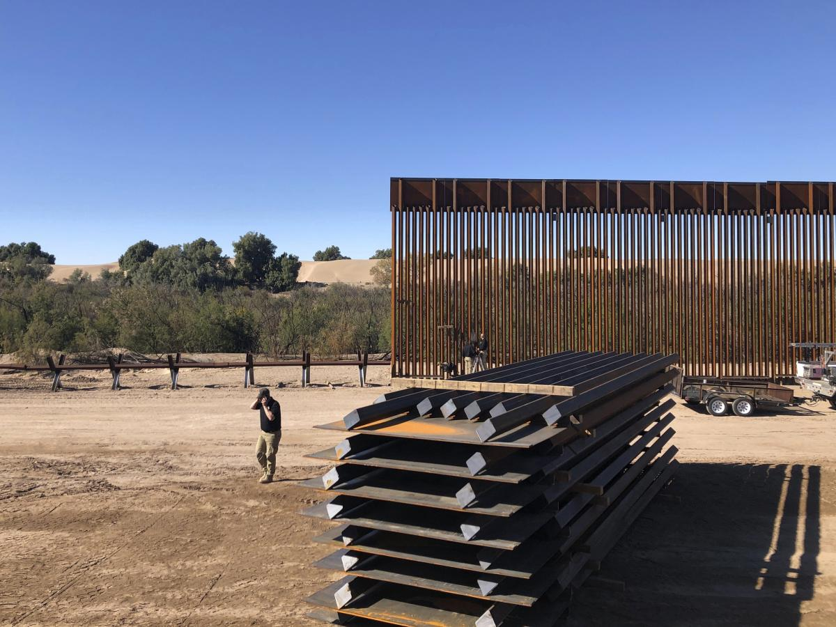 People work at a portion of border wall which is under construction in Yuma, Ariz. Illegal border crossings have plummeted as the Trump administration has extended a policy to make asylum seekers wait in Mexico for court hearings in the U.S.