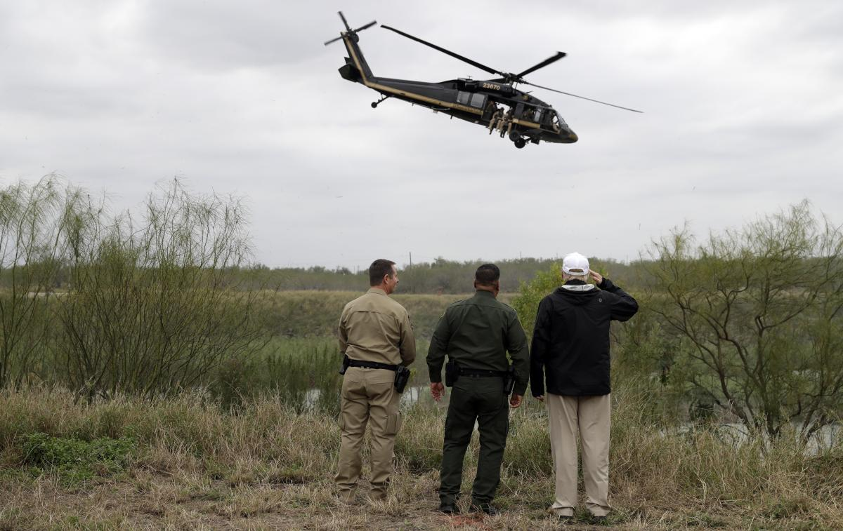 President Trump salutes a U.S. Customs and Border Protection helicopter as he tours the U.S. border with Mexico at the Rio Grande on Thursday in McAllen, Texas.