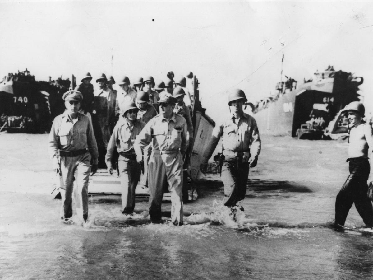 General Douglas MacArthur goes ashore from a landing craft with a party of the invading force at Luzon. This photo, taken in 1945, shows MacArthur reenacting a a similar scene from 1944.