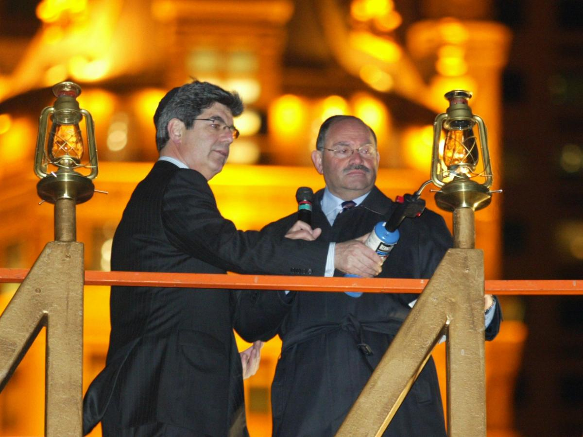 Allen Weisselberg (right), the longtime chief financial officer of the Trump Organization, lights a Hanukkah menorah with then-Macy's CEO Ron Klein in 2004 in New York City.