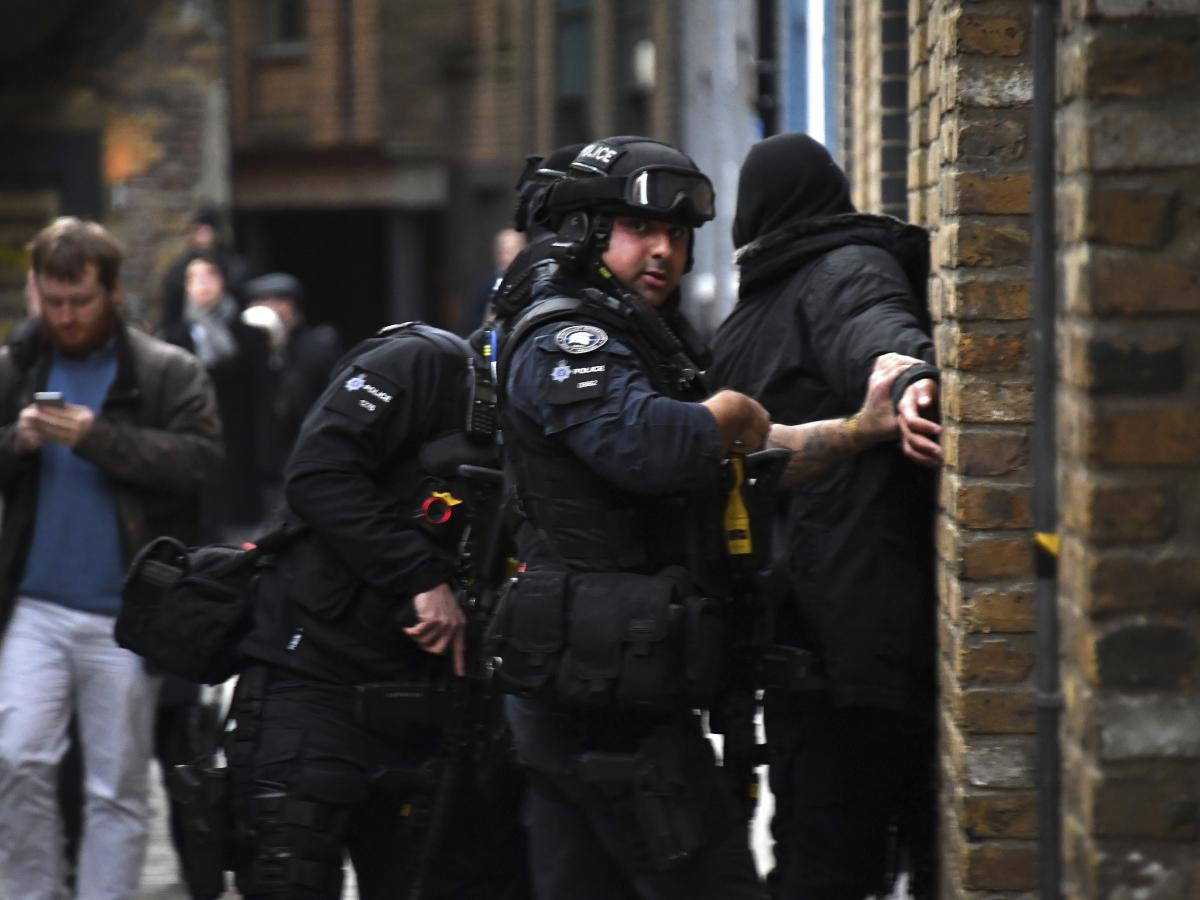 Police apprehend a man in an street on the south side of London Bridge in London, on Friday.