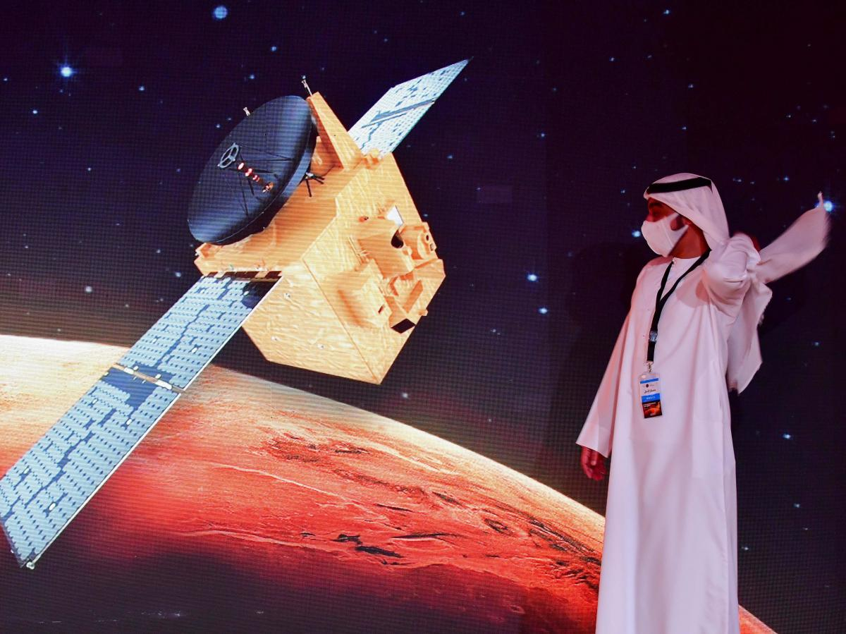 """An Emirati walks past a screen displaying the """"Hope"""" Mars probe at the Mohammed Bin Rashid Space Centre in Dubai, on Sunday."""