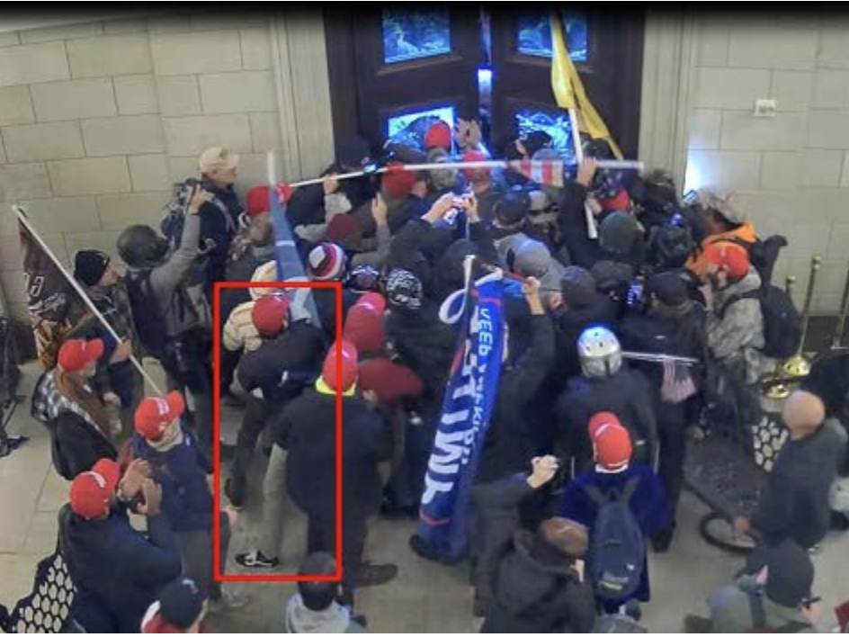 The Justice Department says Christian Secor can be seen in surveillance footage from inside the U.S. Capitol on Jan. 6. Charging papers include this screen grab, allegedly showing Secor pushing against Capitol Police officers along with other members of t