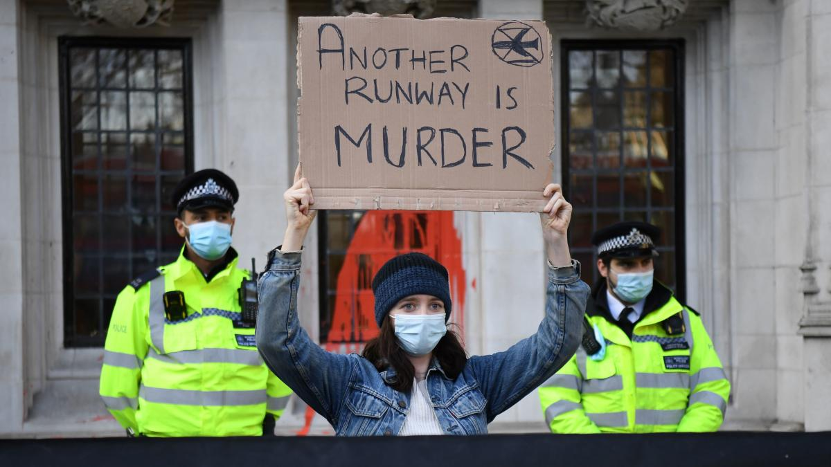 A demonstrator raises a sign protesting plans for a third runway in London, the same day that the British Supreme Court reopened the door to the runway. The runway had previously been blocked on environmental grounds.