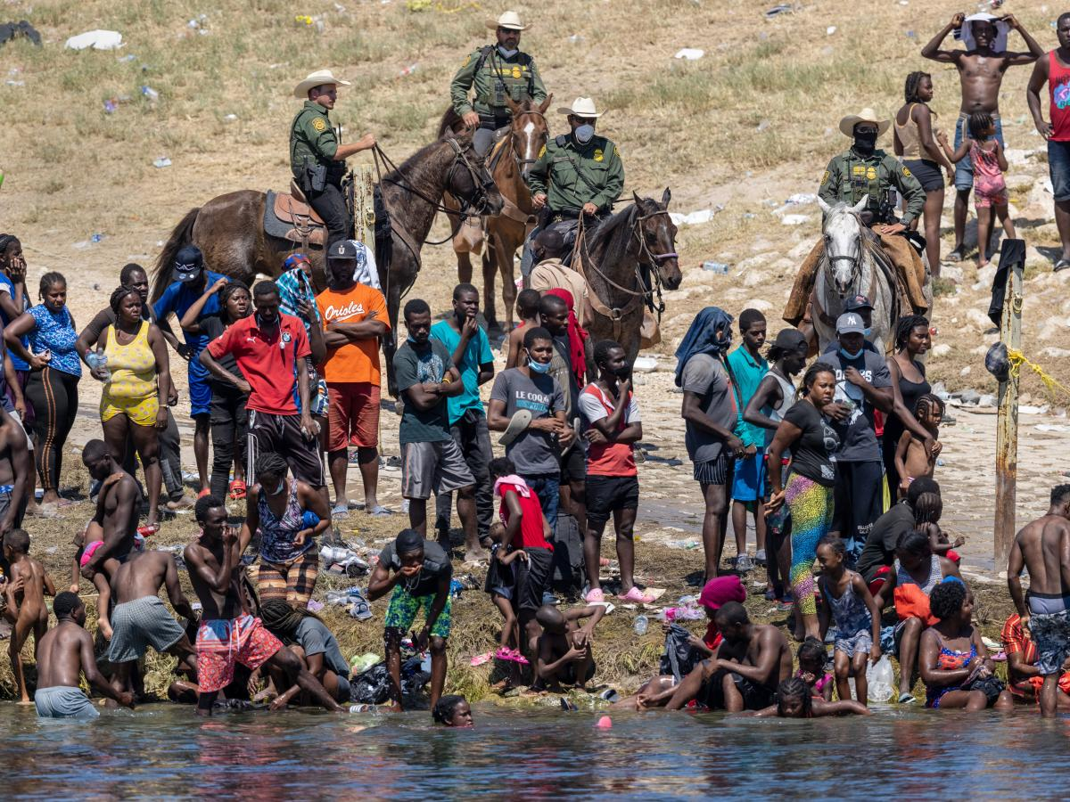 Mounted Border Patrol agents watch Haitian migrants Monday on the banks of the Rio Grande in Del Rio, as seen from Ciudad Acuña, Mexico.