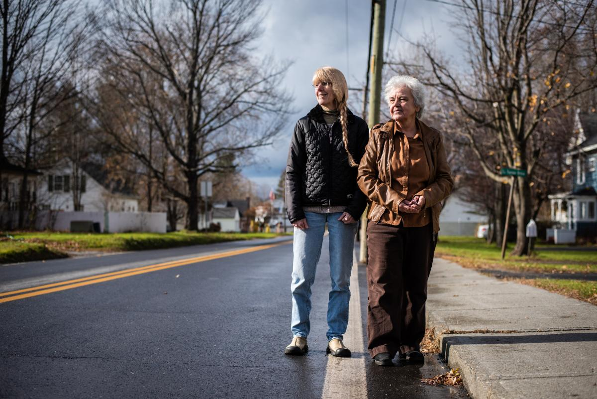 Neighbors Janice Beadle (left) and Marie Vallieres stand on their respective sides of the white stripe that marks the international border on Canusa Avenue, with the U.S. on the left and Canada on the right.