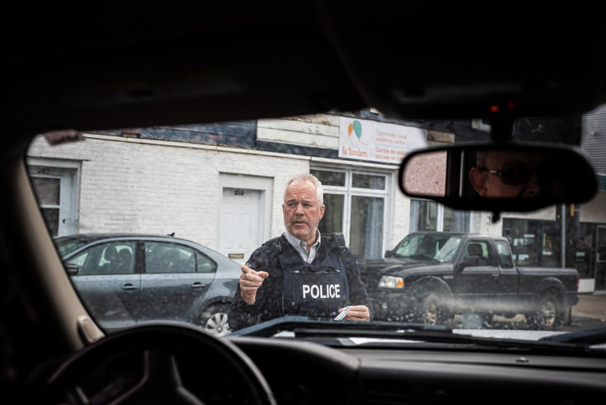 A member of the Royal Canadian Mounted Police holds Scott Wheeler's identification while asking another officer to collect the passports of Wheeler's passengers. Wheeler was pulled over after inadvertently driving into Canada from Canusa Avenue, which str