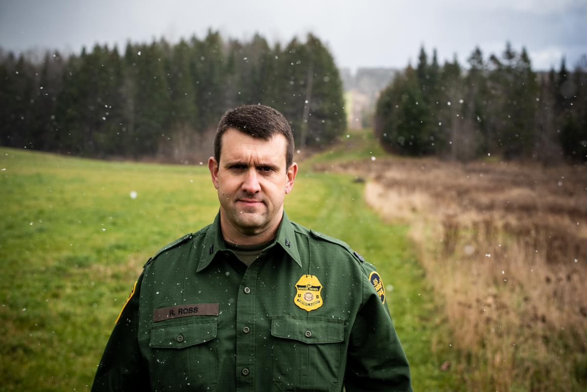 Richard Ross, patrol agent in charge of the United States Border Patrol's Newport Station, stands near the international boundary, marked by the slash in the forest.