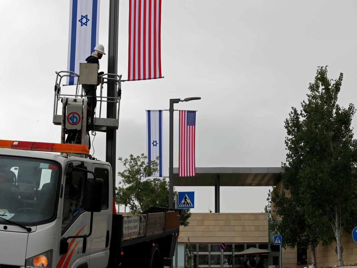 A worker installs decorations of Israeli and US flags on Monday.