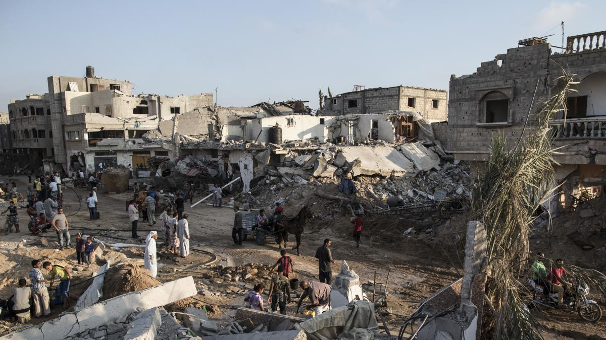 Palestinians walk through an area of destruction on August 15, 2014 in Khuza'a, Gaza. A new report from Amnesty International alleges that during the summer 2014 war between Israel and Hamas, under the cover of conflict, Hamas executed at least 23 Palesti