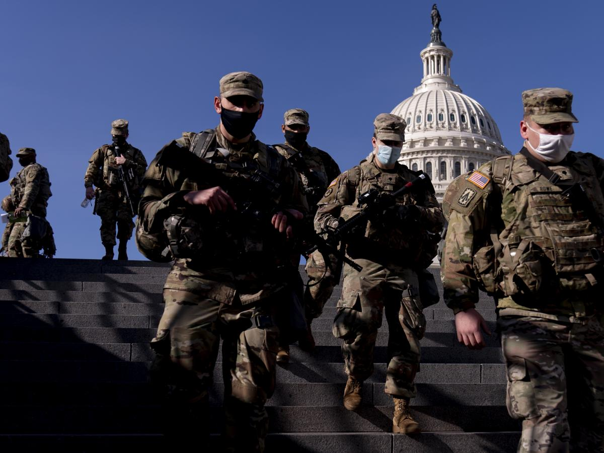 Members of the National Guard walk past the Capitol in Washington on Thursday. By next week, they will be joined by thousands of others.