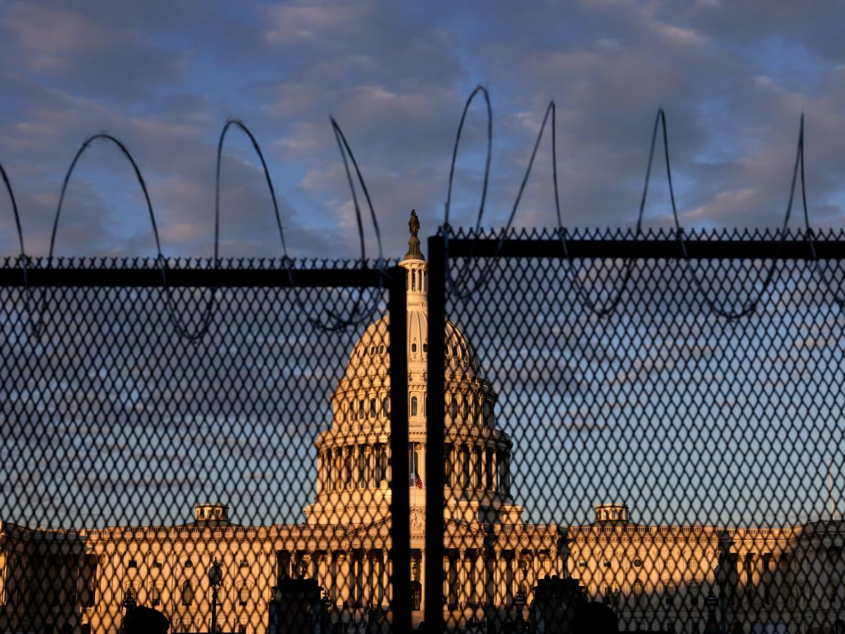 The U.S. Capitol is seen behind a fence with razor wire during sunrise Saturday. The FBI has warned of additional threats in the nation's capital and in all 50 states.