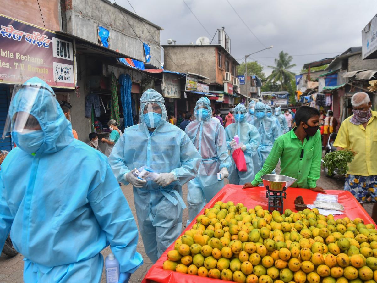 Medical staff along with volunteers from the Hindu hard-line group Rashtriya Swayamsevak Sangh walk through a market for a door-to-door medical screening in Mumbai, India, on June 17.