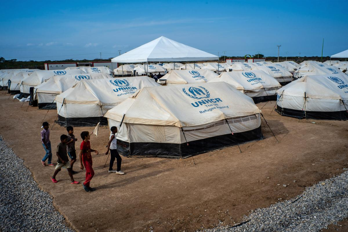 Venezuelan children walk past tents at the United Nations refugee agency camp in La Guajira, Colombia, in April. Local and national government agencies called on the UNHCR for aid after tens of thousands of Venezuelan migrants and refugees crossed the bor