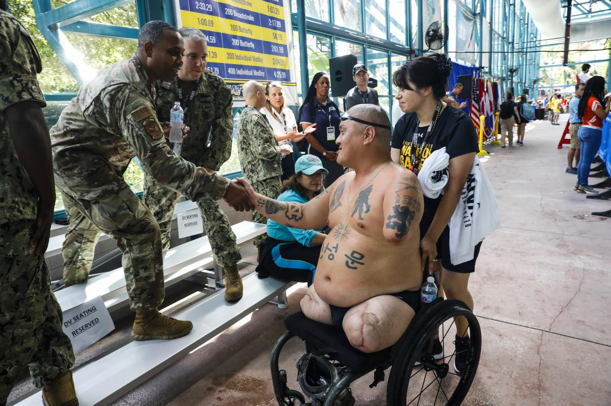"""Matt shakes hands with members of the Warrior Games community after his race. """"I got a letter saying that I was out of the [caregivers] program because the veteran hasn't shown any progress since 2011,"""" Alicia said. """"I asked them, 'What do you mean by pro"""