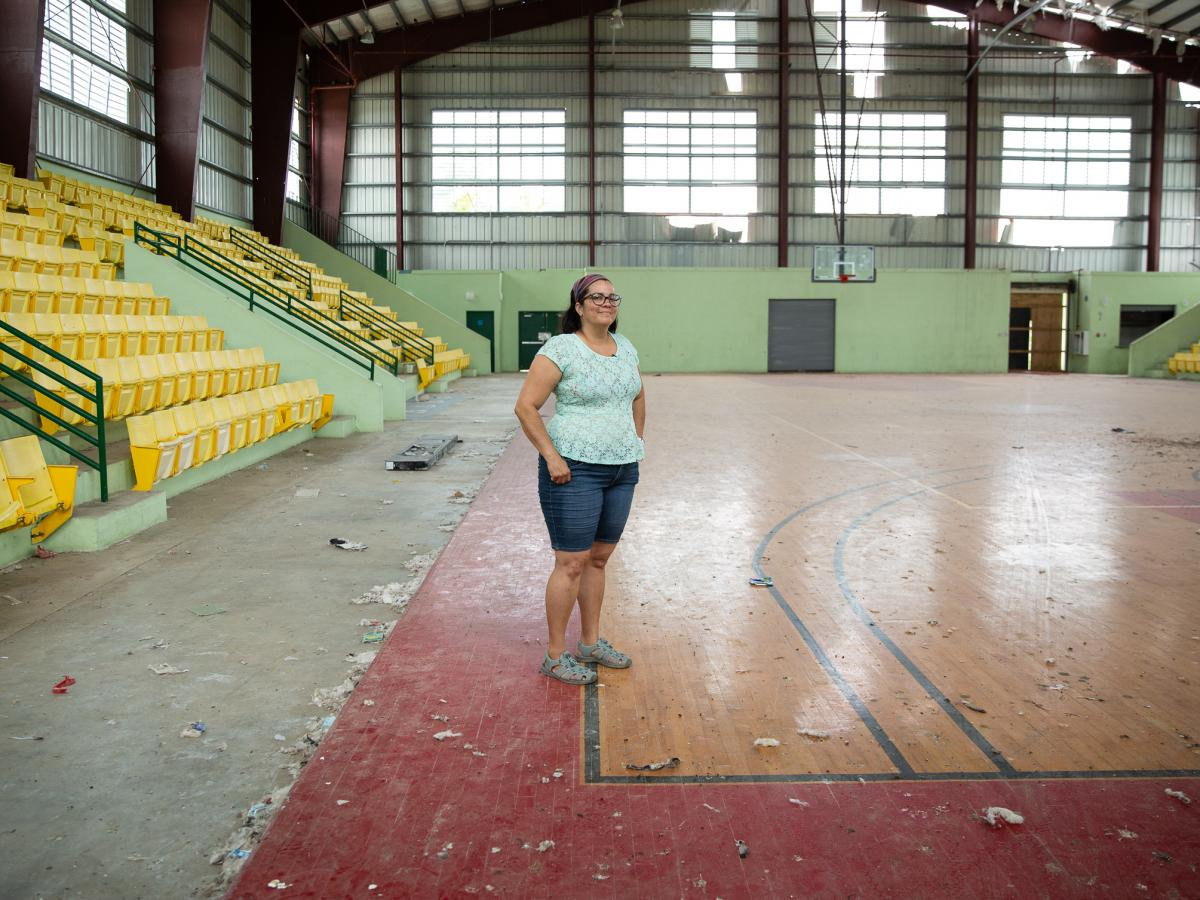 Elda Guadalupe Carrasquillo, a municipal legislator and a middle school science teacher in Vieques, Puerto Rico, stands on the island's only wooden basketball court. It was wrecked during Hurricane Maria. Since then, it's only been used by birds and roami