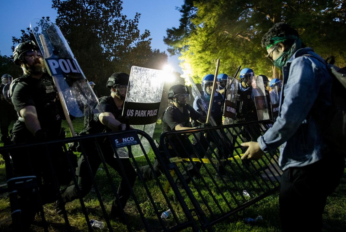 Police move forward to raise a barrier that protesters had knocked down in front of the White House on Sunday.