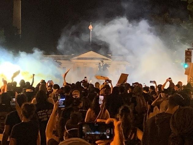 Protesters in Washington, D.C., Sunday night with the White House North Portico visible through clouds of tear gas.
