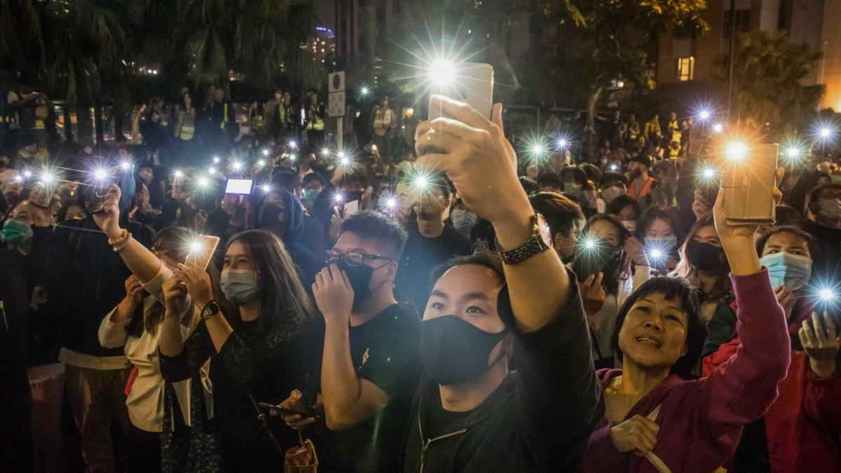 People raise their mobile phones during a demonstration Monday evening local time, near an area cordoned off by police in Hong Kong.