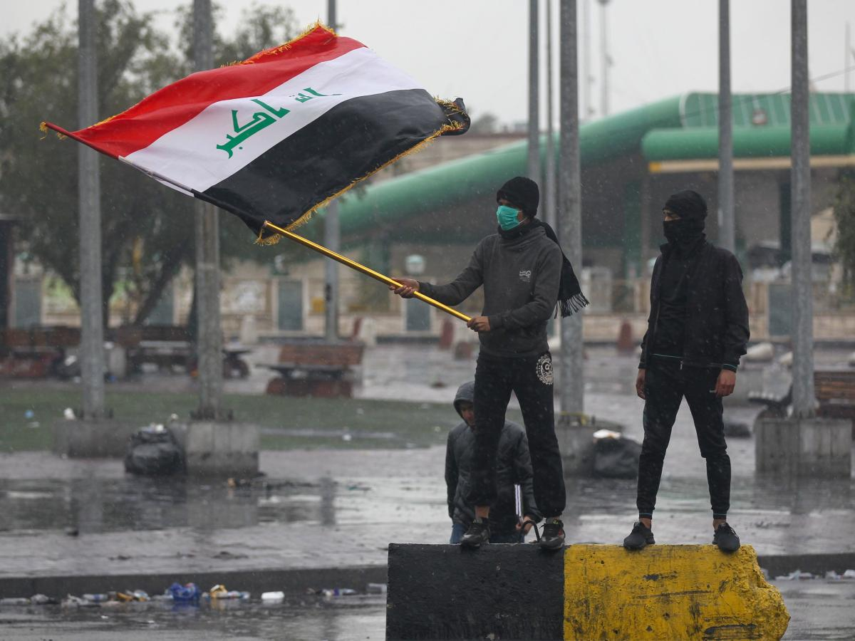 An Iraqi protester waves the national flag during demonstrations in east Baghdad on Wednesday. Protesters have shut roads to pressure authorities to implement long-awaited reforms.