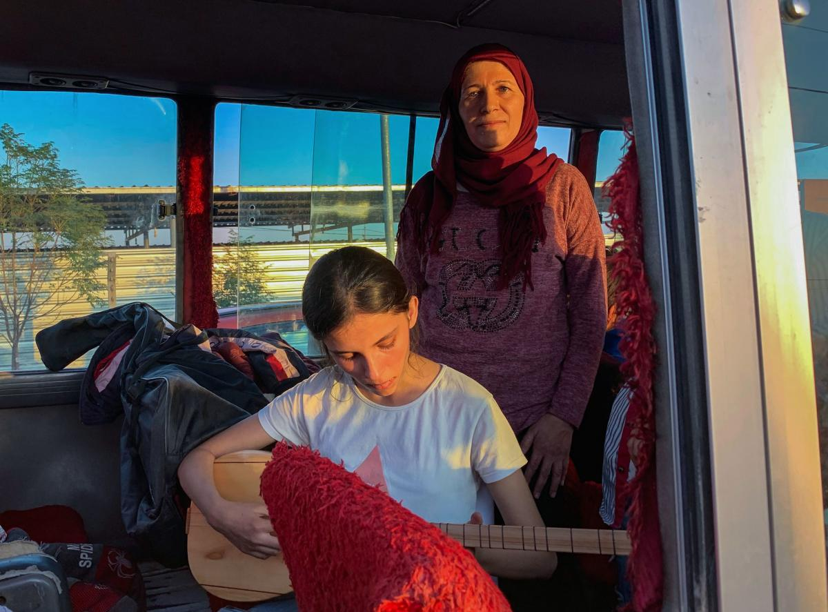 """""""We brought our ambitions,"""" says Najah Raso. She and her daughter, Solin, 14, holding a Kurdish lute, were on a bus of refugees arriving from the Syrian border to a camp in the Kurdistan region of Iraq this week. More than 2,000 people arrived in Iraq ove"""
