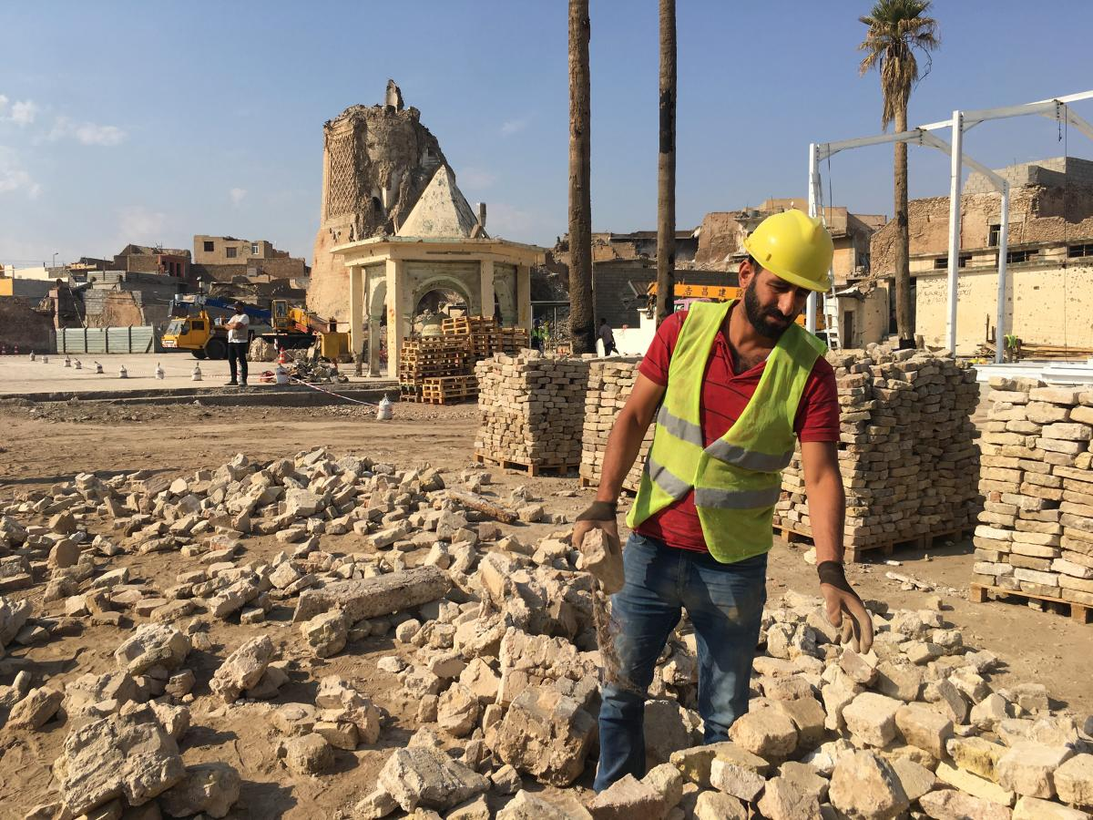 A worker in Mosul, Iraq, assesses the damage in the al-Nuri Mosque compound. Workers are reconstructing the mosque's al-Hadba minaret.